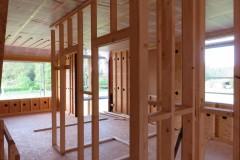 Binnenmuren in opbouw, sls. De wanden halen hun stevigheid uit de OSB. De gaten zijn om cellulose in te spuiten.